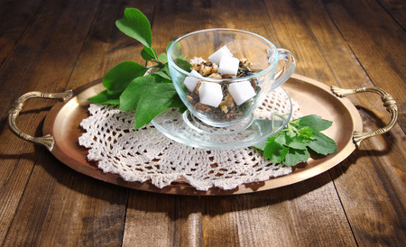 Glass cup with dry flowers and herbs, fruits ingredients for tea, on tray, on color wooden background photo