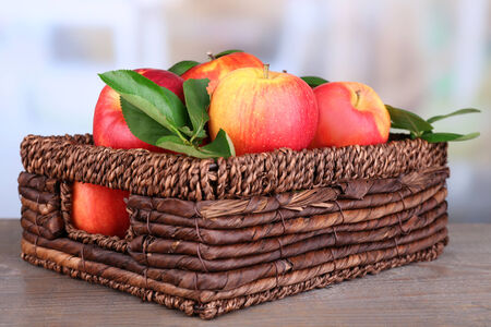 Ripe sweet apples with leaves in wicker crate on light background photo
