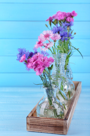 Beautiful summer flowers in vases on blue wooden background photo