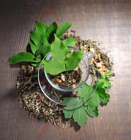 Glastasse mit trockenen Blumen und Kr�utern, Fr�chten Zutaten f�r Tee, Farbe auf Holzuntergrund photo