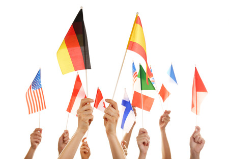 Hands holding different flags, isolated on white photo