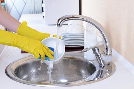 wash dishes: Close up manos de lavar los platos en la cocina de la mujer