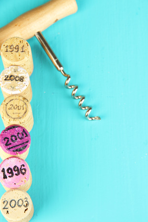 Wine corks with corkscrew on wooden table close-up photo