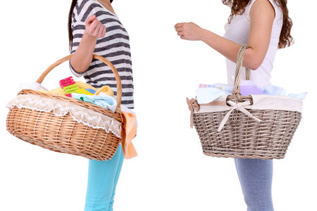 Women holding laundry baskets with clean clothes, towels and pins, isolated on white photo