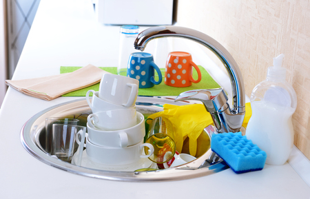 Stack of dishes soaking in kitchen sink photo