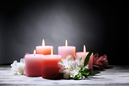 Beautiful candles with flowers on wooden table, on dark background photo