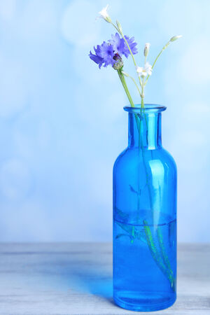 Bright wildflower in bottle on wooden table, on light background photo