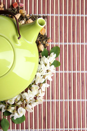 Herbal natural floral tea infusion with dry flowers and herbs ingredients, on bamboo mat background photo