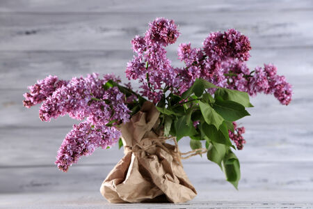 Beautiful lilac flowers in vase, on color wooden background photo