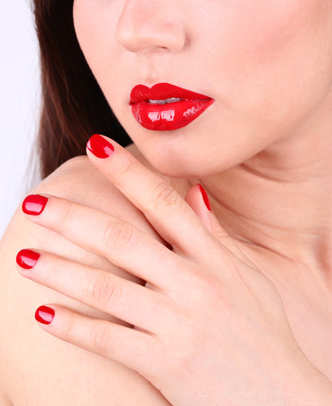 Girl with red lips and nails, closeup photo