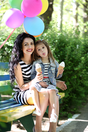 Happy mom and daughter. Walk in the green park Foto de archivo