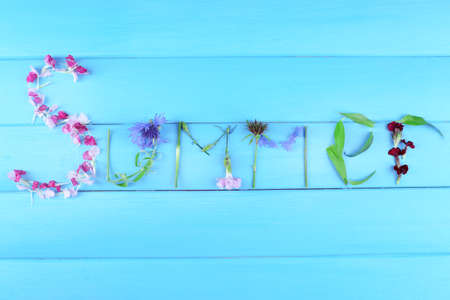 Inscription summer from leaves and flowers on wooden background photo