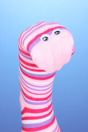 Cute sock puppet on blue background Stock Photo