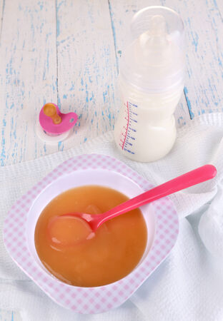 Baby food and milk on wooden table photo