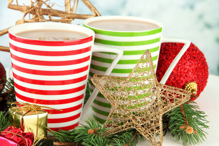 Cups of hot cacao with Christmas decorations on table on bright background photo