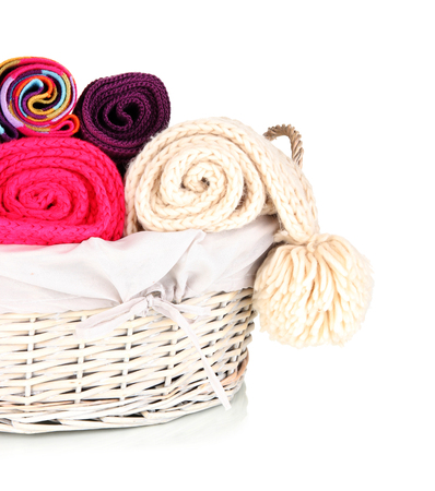 clothes interesting: Warm knitted scarves in basket isolated on white