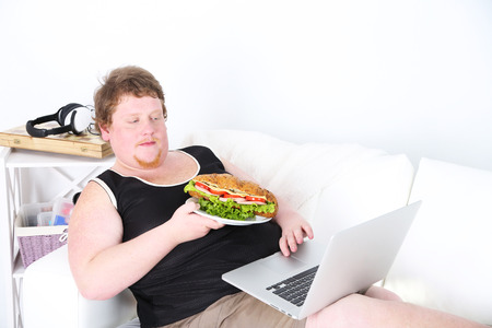 Fat man sitting with laptop on sofa and eating tasty sandwich on home interior background 版權商用圖片