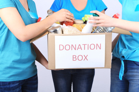 aliments: Volontaires avec bo�te de dons avec les denr�es alimentaires sur fond gris