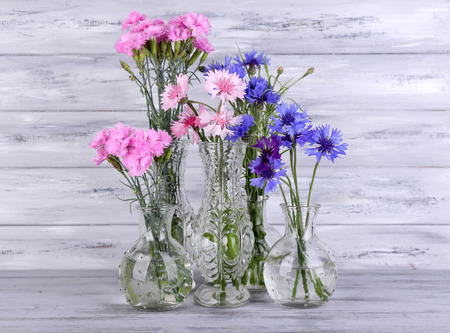 Beautiful Summer Flowers In Vases On Grey Wooden Background Stock