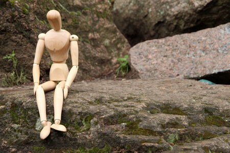 Wooden pose puppet sitting on stone, outdoors photo