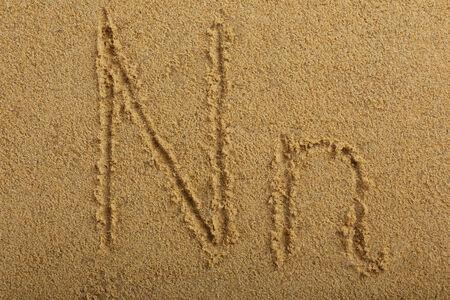 Alphabet letter written on wet beach sand photo