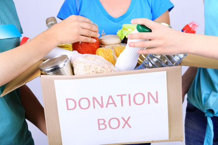foodstuffs: Volunteers with donation box with foodstuffs on grey background