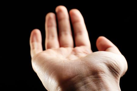 reverent: Human hand on black background Stock Photo