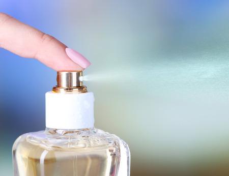 Bouteille de parfum dans la main sur fond clair
