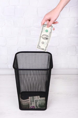 Throwing away your money on grey wall background photo