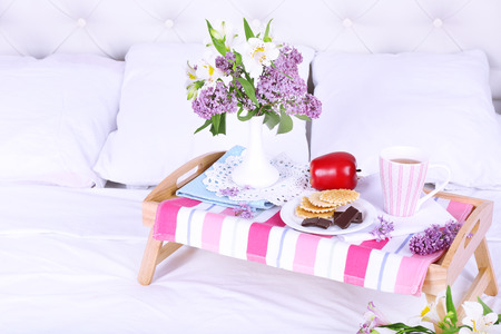 Light breakfast and beautiful bouquet on bed photo