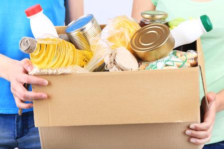 viveres: Los voluntarios con caja de donaciones con alimentos sobre fondo gris