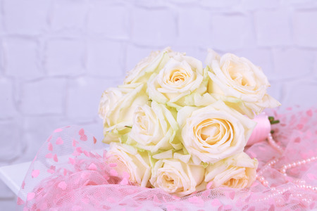 Beautiful wedding bouquet with roses on grey wall background photo