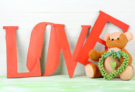 Decorative letters forming word LOVE with teddy bear on wooden background photo