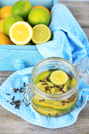 Pickled limes and cloves in glass jar, on color wooden background photo