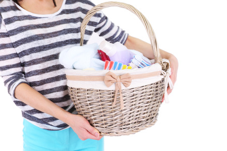 wicker work: Woman holding laundry basket with clean clothes, towels and pins, isolated on white