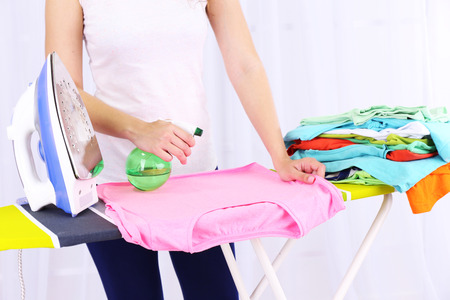 Woman ironing clothes on ironing board, close-up, on light background photo