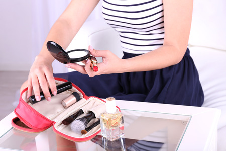 Girl applying make up on home interior background photo