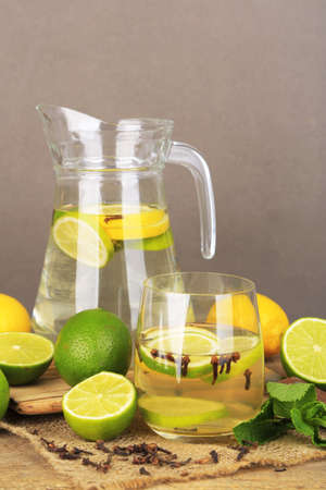 Fresh summer drink with lime and cloves in glass and jug, on color wooden table, on bright background photo