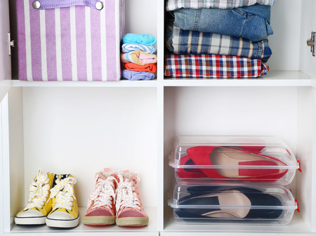 Clothes and shoes on shelves close-up photo