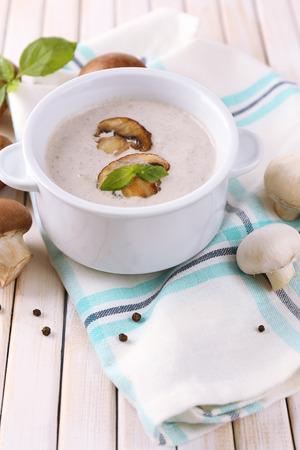 Mushroom soup in white pot, on napkin, on wooden background photo