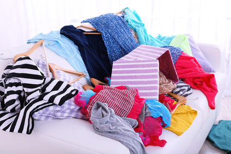 disorganized: Messy colorful clothing on  sofa on light background