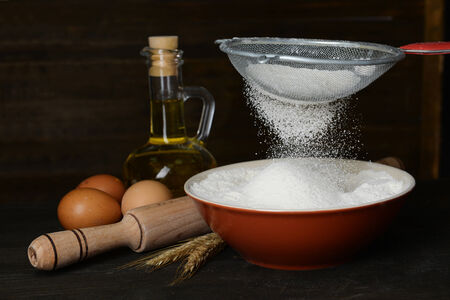 Sifting flour into bowl on table on wooden background photo