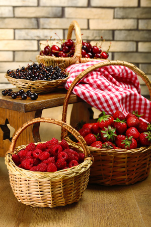 Fresh berries in basket on wall background photo