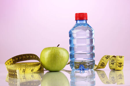 microelements: Bottle of water, apple and measuring tape on purple background