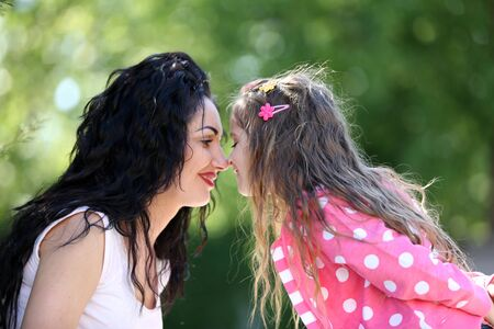 Happy mom and daughter. Walk in the green park Stock Photo