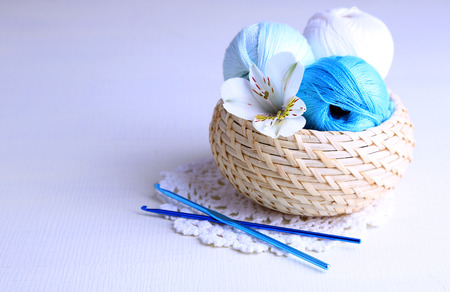 basket embroidery: Colorful clews and crochet hooks in wicker basket on wooden background Stock Photo