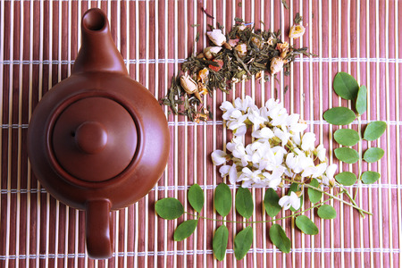 Herbal natural floral tea infusion with dry flowers ingredients, on bamboo mat background photo