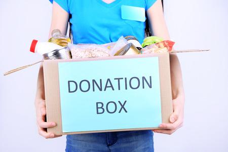 viveres: Voluntariado con caja de donaciones con alimentos sobre fondo gris