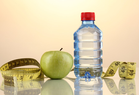 microelements: Bottle of water, apple and measuring tape on orange background