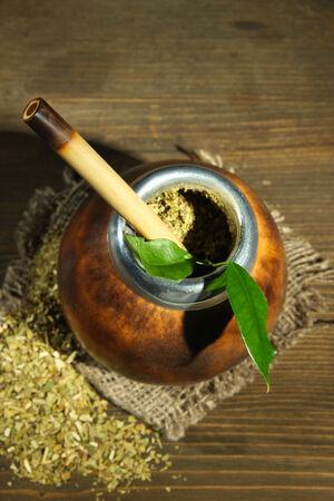 yerba mate: Calabaza y bombilla con yerba mate en el fondo de madera gris